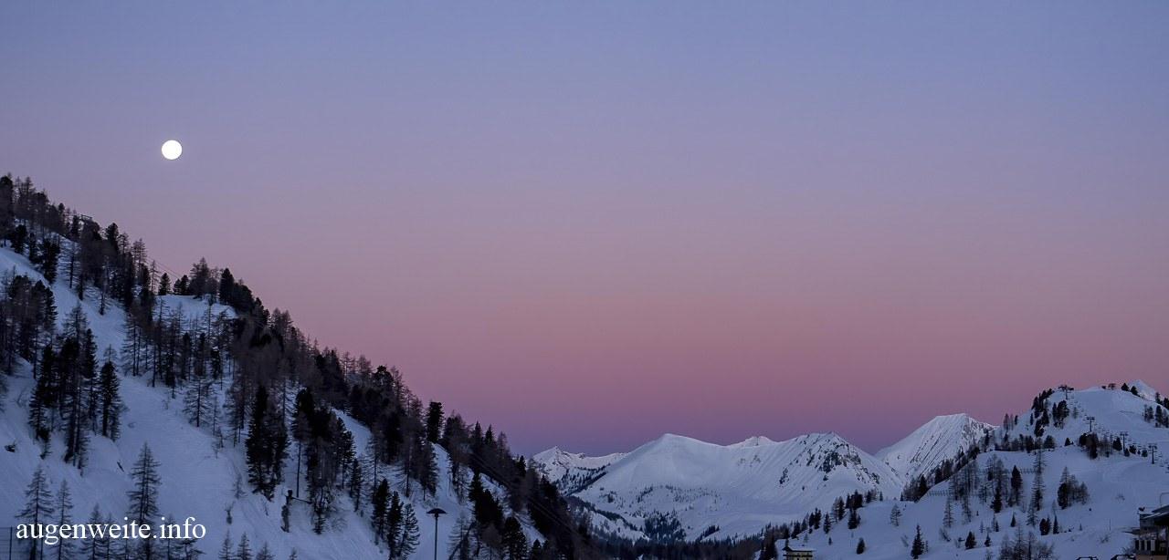 Mond über Bergen im Morgengrauen